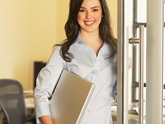 Smiling woman carrying laptop